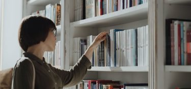 man in brown long sleeve shirt holding book in white wooden book shelf